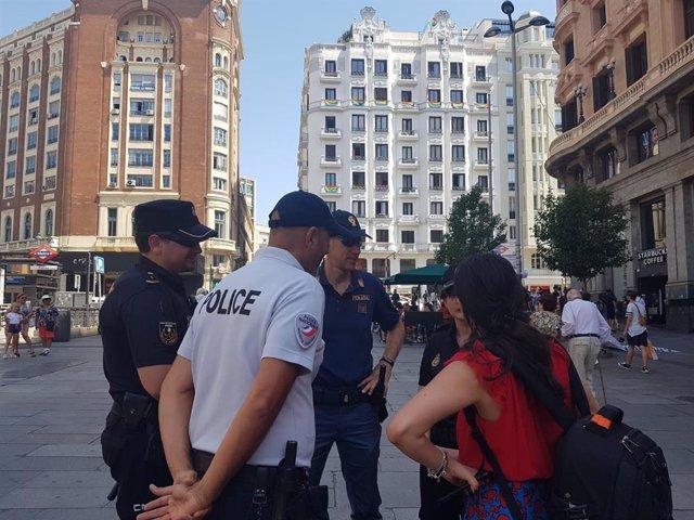 Archivo - Agentes de la Policía Nacional y agentes franceses atienden a turistas en el centro de la capital