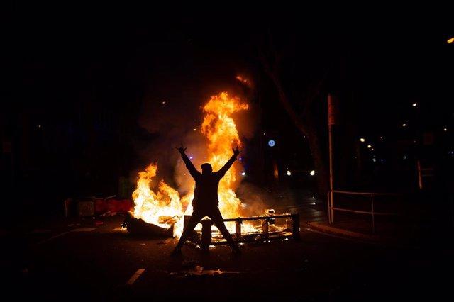 Una persona ante una hoguera durante los altercados producidos en una manifestación contra el encarcelamiento del rapero y poeta Pablo Hasel, en los Jardines de Gracia, en Barcelona, Catalunya (España), en una imagen de archivo del 17 de febrero de 2021.