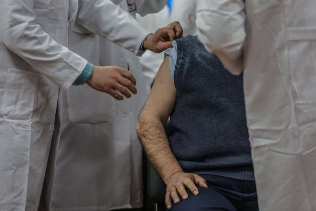 22 February 2021, Palestinian Territories, Gaza City: A Palestinian medic receives a dose of the Sputnik V COVID-19 vaccine, during a vaccination campaign. On Sunday, Mohammad Dahlan, the rival of Palestinian Authority President Mahmoud Abbas, brokered th