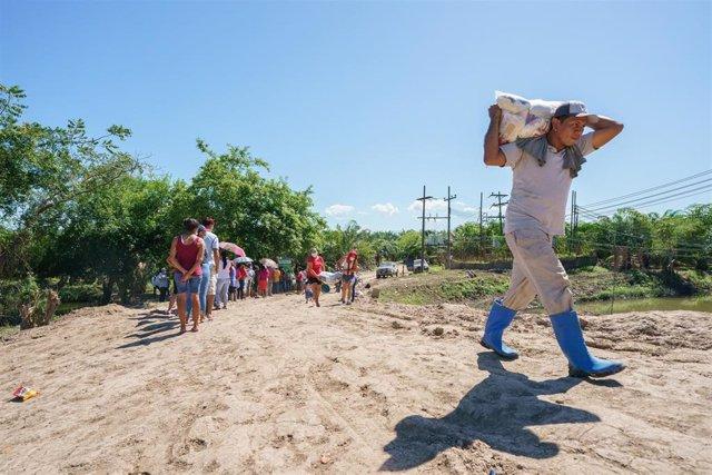 Un hombre carga cerca de Coloma en Honduras con ayuda humanitaria.