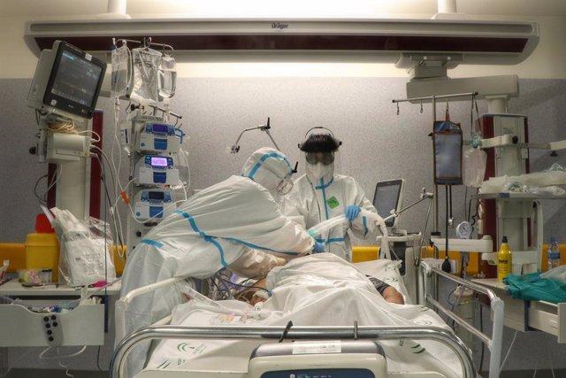 Archivo - Arxiu - Facultatius atenen a un pacient amb Covid-19 en la UCI de l'Hospital Regna Sofia de Còrdova.