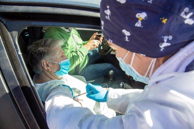 Una sanitaria inyecta la vacuna de Pfizer a una persona mayor que espera desde el coche en el exterior del Polideportivo Municipal, en Villafranca De Los Barros, Badajoz, Extremadura (España), a 15 de febrero de 2021