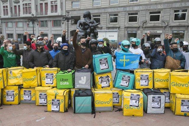 Varios repartidores acumulan sus mochilas tras haber participado en una pitada en sus vehículos, convocados por Repartidores Unidos y APRA en Oviedo.
