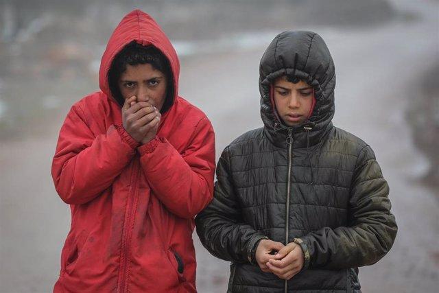Archivo - Varios niños se calientan las manos en el campo de refugiados de Barisha, al norte de Siria.