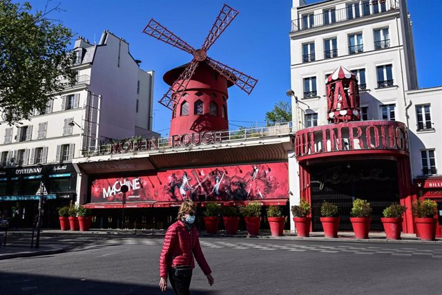 Archivo - Una mujer con mascarilla pasa frente al Molino Rojo de París, en Francia