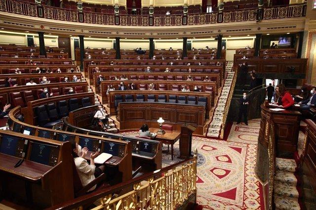 Componentes del hemiciclo aplauden, a excepción de Vox y algunos miembros del PP, durante la lectura de los nombres de las 1081 mujeres asesinadas por violencia de género en España desde 2003, en una sesión plenaria en el Congreso de los Diputados, en Mad