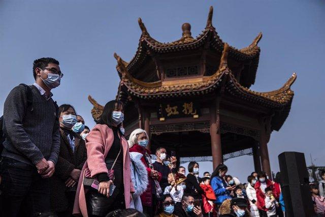 Un grupo de personas con mascarilla ve uno de los espectáculos callejeros del primer día del nuevo año lunar en Wuhan (China).