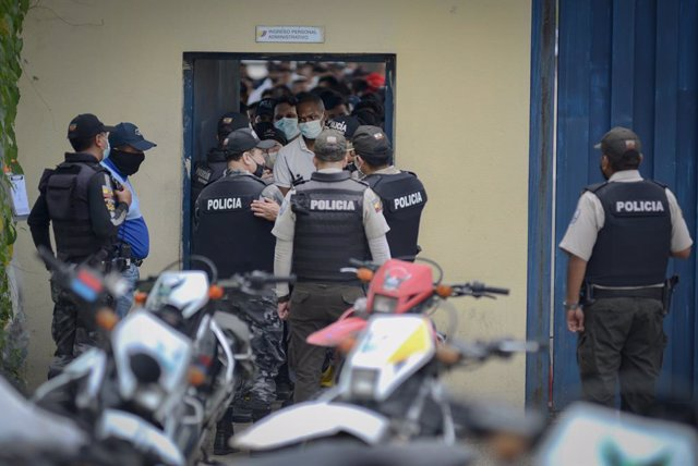23 February 2021, Ecuador, Guayaquil: Police officers are on duty at a prison after a mutiny while relatives of the inmates wait outside for information. At least 50 people have been killed in several prison mutinies in Ecuador, according to police on Tue