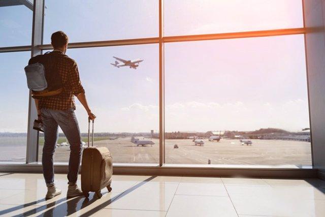 Viajero en ventana de aeropuerto viendo despegar un avión
