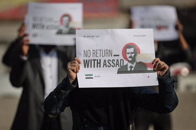 Archivo - 12 November 2020, Syria, Sarmada: Internally displaced persons and employees of civil society organizations hold placards demanding Syrian President Bashar al-Assad to step down so that they can return, during a protest against the international