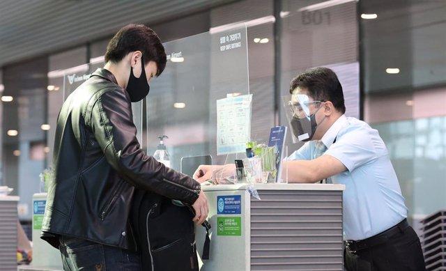 Archivo - Un pasajero muestra el certificado de un resultado negativo de un test de coronavirus a un empleado del aeropuerto internacional de Incheon, en Corea del Sur