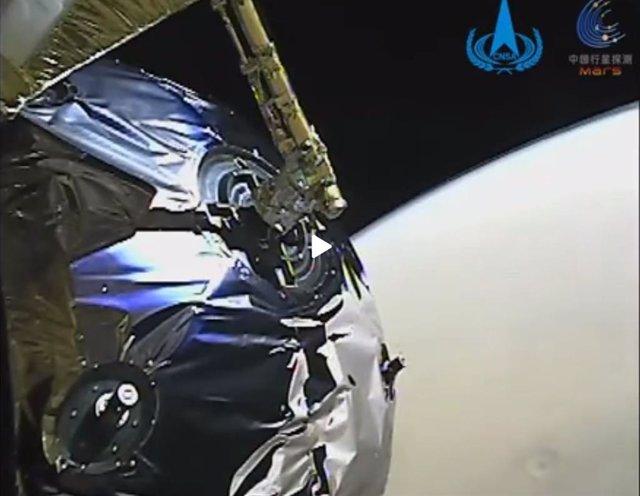 Tianwen 1 durante la inserción orbital en Marte. En la imagen se aprecia un cráter en la superficie.