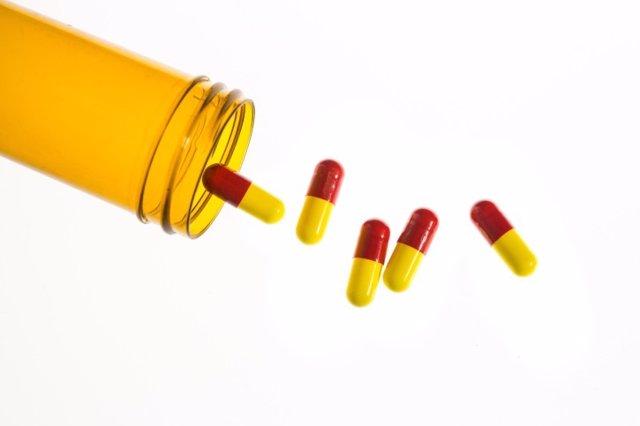 Archivo - Jar of medicine spilling capsule tablets