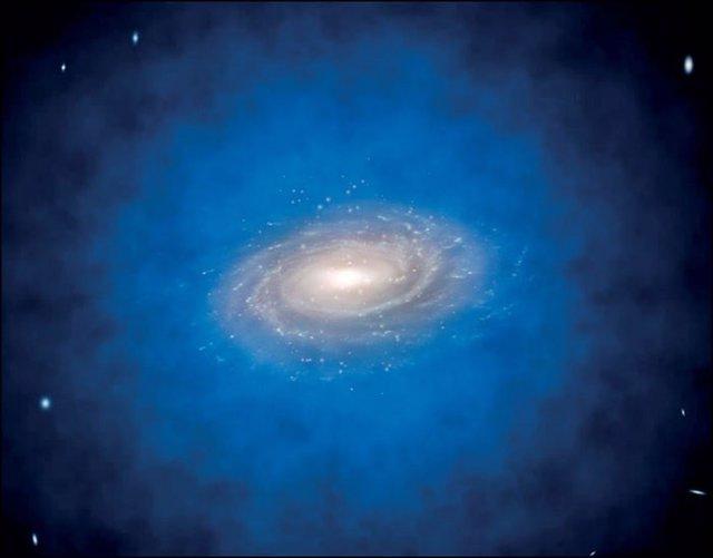 Impresión artística de una galaxia espiral incrustada en una distribución más grande de materia oscura invisible, conocida como halo de materia oscura (de color azul).