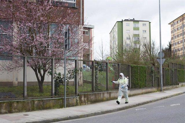 Una persona desinfecta el perímetro que rodea el colegio público CEIP  Paradai, en Lugo, Galicia (España), a 19 de febrero de 2021. Sanidad de Lugo confirmó ayer que ascienden a 60 los positivos de un brote vinculado al colegio Paradai de Lugo, entre esco