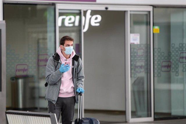 Archivo - Un hombre con mascarilla y guantes carga con una maleta en la Estación del Norte al inicio de la segunda semana del estado de alarma, en Valencia / Comunidad Valenciana (España), a 23 de marzo de 2020.
