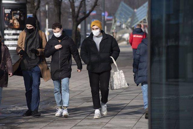 Tres personas caminan por la calle en Varsovia.