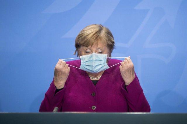 Archivo - Angela Merkel se quita la mascarilla en una rueda de prensa en Berlín