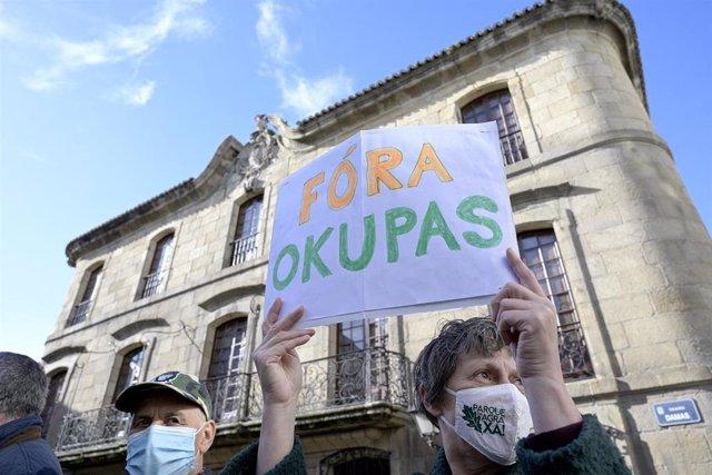 """Archivo - Una persona sostiene un cartel donde se puede leer """"Fuera okupas""""."""