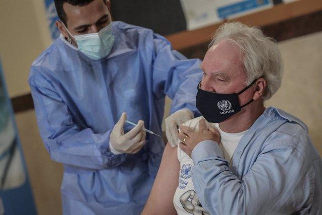 El director de la Agencia de Obras Públicas y Socorro de Naciones Unidas para los Refugiados de Palestina, Matthias Shamali, recibe la vacuna contra el coronavirus en Gaza.
