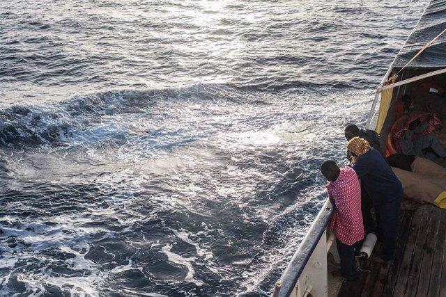 Refugiados y migrantes miran por la borda en el Mediterráneo desde la borda del Open Arms tras un rescate realizado la semana pasada.
