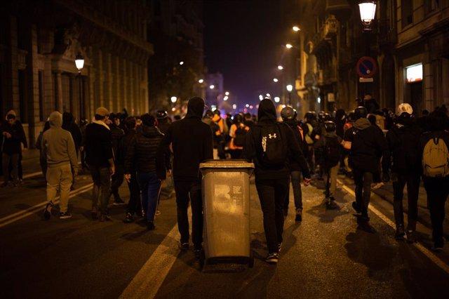 Joves violents arrosseguen una galleda d'escombraries després de la manifestació contra l'empresonament del raper i poeta Pablo Hasel, a Barcelona, Catalunya (Espanya), a 19 de febrer de 2021.