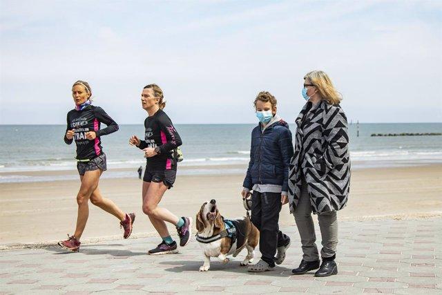Archivo - Dos mujeres corren por la playa mientras que una mujer y un niño pasean un perro en una imagen de archivo de las playas de Dunkerque.