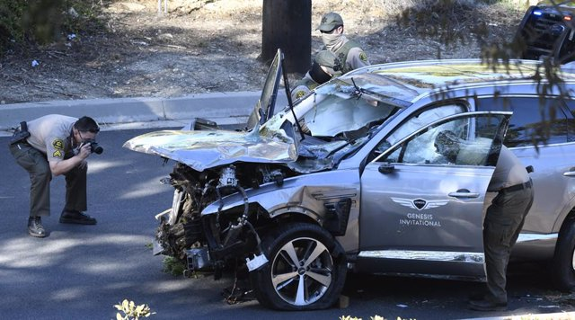 23 February 2021, US, Rancho Palos Verdes: Police inspect the damaged car of American professional golfer Tiger Woods after he was involved in a vehicle rollover crash on the border of Rolling Hills Estates. Woods suffered multiple leg injuries, and was u