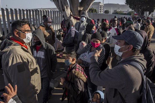 19 February 2021, Mexico, Tijuana: Migrants wait at the El Chaparral border crossing between Mexico and the US. Starting from today, the new US administration under US President Joe Biden will gradually allow the entry and stay of the last 25000 asylum se