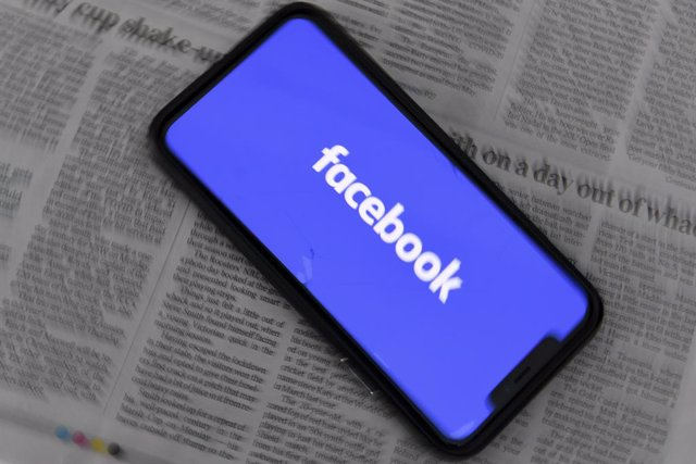 An illustration image shows a phone screen with the 'Facebook' logo seen at Parliament House in Canberra, Thursday, February 18, 2021. Social media giant Facebook has moved to prohibit publishers and people in Australia from sharing or viewing Australian
