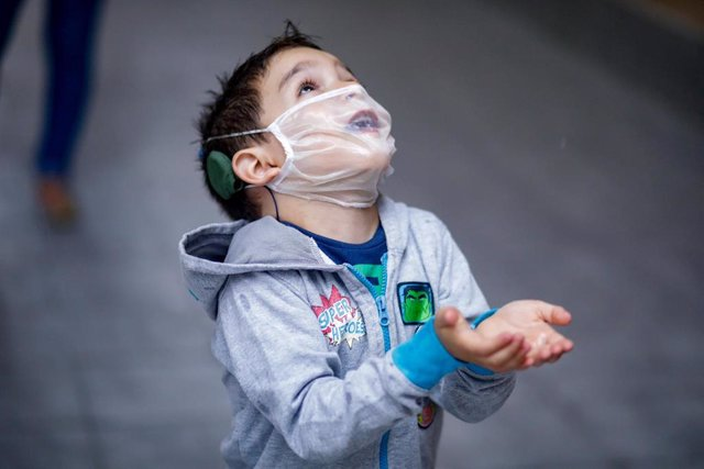 Archivo - El pequeño Hugo Romero, sordo profundo y usuario de 2 implantes cocleares, utiliza una mascarilla transparente certificada -pero no homologada por el Ministerio de Sanidad- con la que se comunica con su familia mientras juega en las instalacione