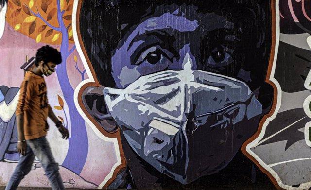 Archivo - Una persona junto a un mural en India durante la pandemia de coronavirus