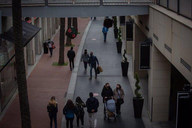 Archivo - Diverses persones passegen per un centre comercial (Arxiu)