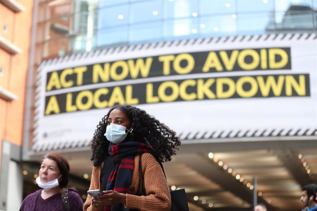 Archivo - 20 October 2020, England, Manchester: A woman wears a face mask walks past by a sign rgarding the upcoming lockdown in Manchester. Greater Manchester will be placed under stricter coronavirus controls after last-ditch talks with the UKPrime Min