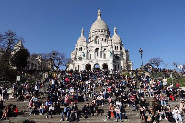 Personas sentadas ante la Basícila del Sacre Coeur en París