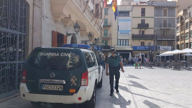 Archivo - Un agente y un vehículo de la Guardia Civil en Inca.