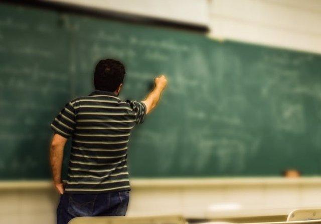 Profesor escribiendo en la pizarra.