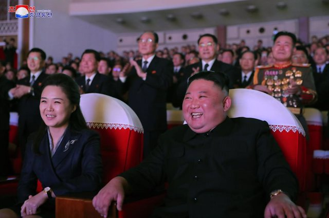 16 February 2021, North Korea, Pyongyang: A photo released by the Korean Central News Agency shows North Korean Leader Kim Jong-un (R) and his wife Ri Sol Ju watching a performance at the Mansudae Art Theater to mark the birthday of Kim's father, Kim Jong