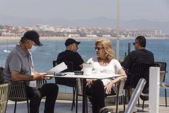 Archivo - Varias personas disfrutan en la terraza de un bar junto a la playa