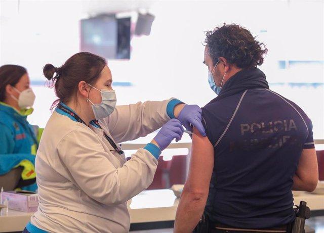 Una sanitaria vacuna a un policía en el punto de vacunación contra el Covid-19