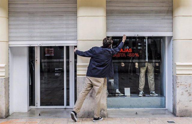 Archivo - El trabajador de un comercio cierra su establecimiento el primer día del cierre total de la hostelería y de tiendas a las 18.00h