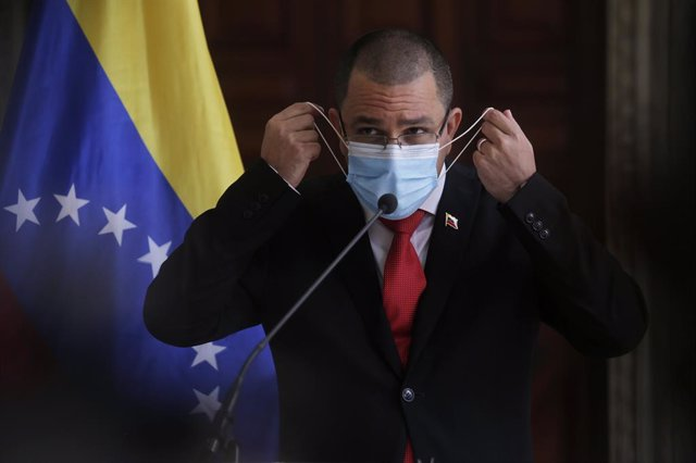 24 February 2021, Venezuela, Caracas: Jorge Arreaza, Foreign Minister of Venezuela, takes off his mask before a press conference at the Foreign Ministry. Photo: Jesus Vargas/dpa