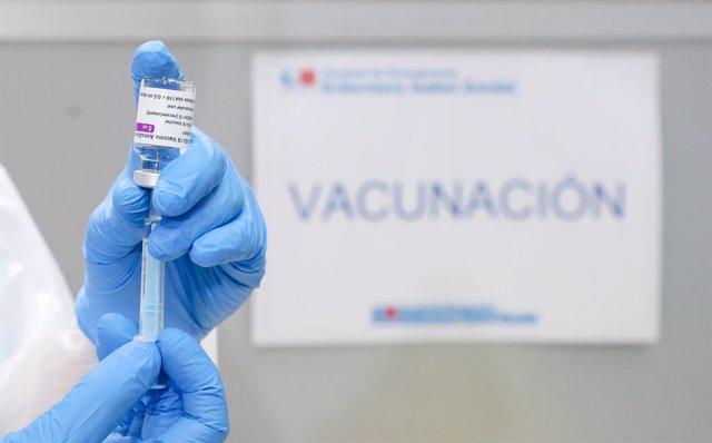 Un profesional sanitario sostiene un frasco con la vacuna contra el COVID-19 de AstraZeneca, en el Pabellón 3 del Hospital Público Enfermera Isabel Zendal, en Madrid, (España), a 23 de febrero de 2021. Este martes comienza la vacunación en el pabellón 3 d