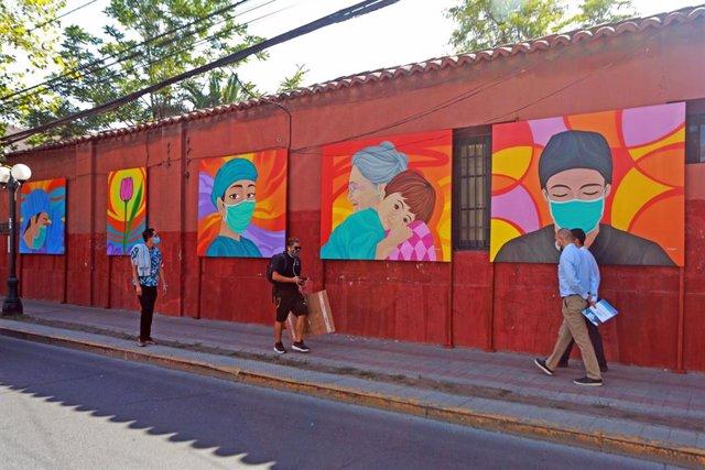 Varias personas caminan al lado de 30 murales realizados en Santiago de Chile por el artista Sebastián Durán para reconocer el esfuerzo de los chilenos contra la pandemia.
