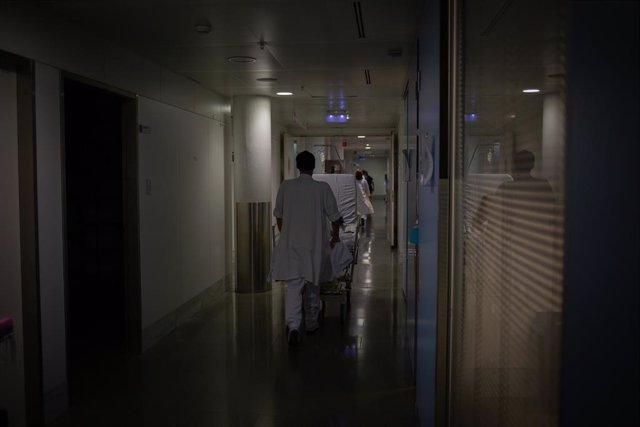 Archivo - Profesional sanitario traslada una cama móvil en la UCI del Hospital de la Santa Creu i Sant Pau, integrado en la Red Hospitalaria de Utilización Pública de Catalunya, en Barcelona, Catalunya (España), a 6 de noviembre de 2020