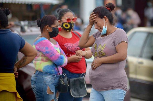 Tres mujeres esperan noticias fuera de la prisión de Guayaquil en Ecuador.