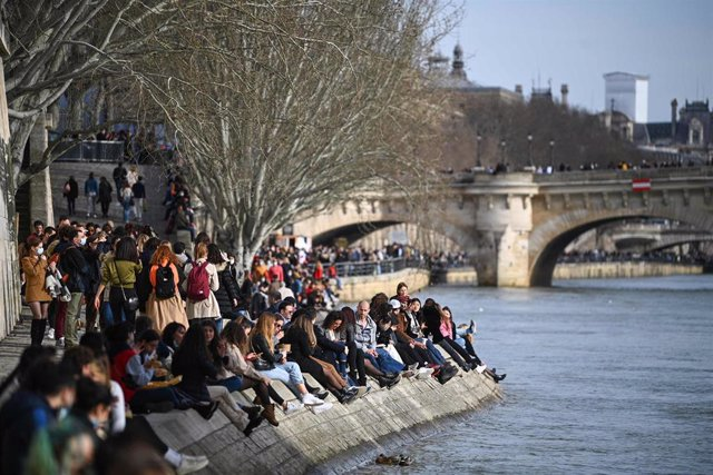 Un grupo de personas se relaja a orillas del Sena.