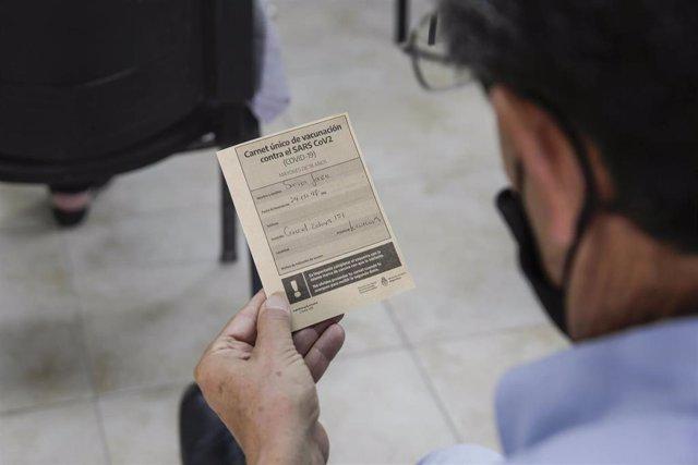 Un hombre lee su tarjeta de vacunación contra la COVID-19.