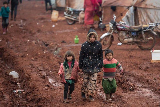Archivo - Niños sirios desplazados caminan sobre barro en el campamento de Marabune en Idlib, Siria.