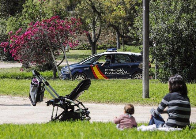 Archivo - Arxive - Una mare asseguda en la gespa al costat de la seua filla veuen passar un cotxe de la Policia Nacional
